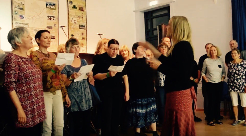 A choir singing led by Rowan Godel